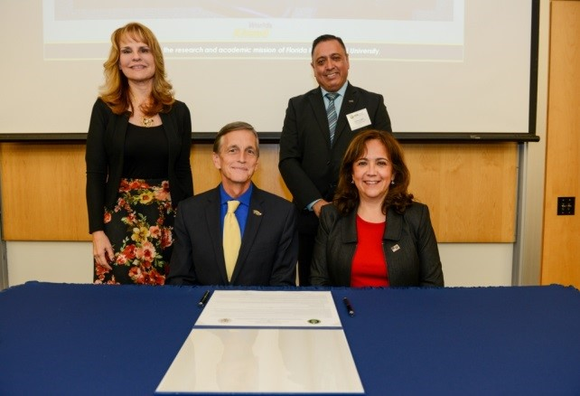 Dr. Ken Furton, Dr. Monica Regalbuto, Dr. Triay and Dr. Lagos signing