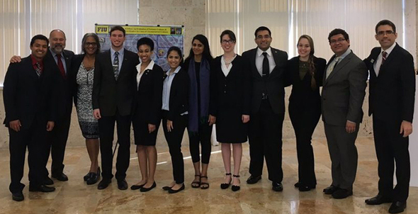 Honors College Associate Dean Espinosa, second from left, with FIU students at a research presentation event.