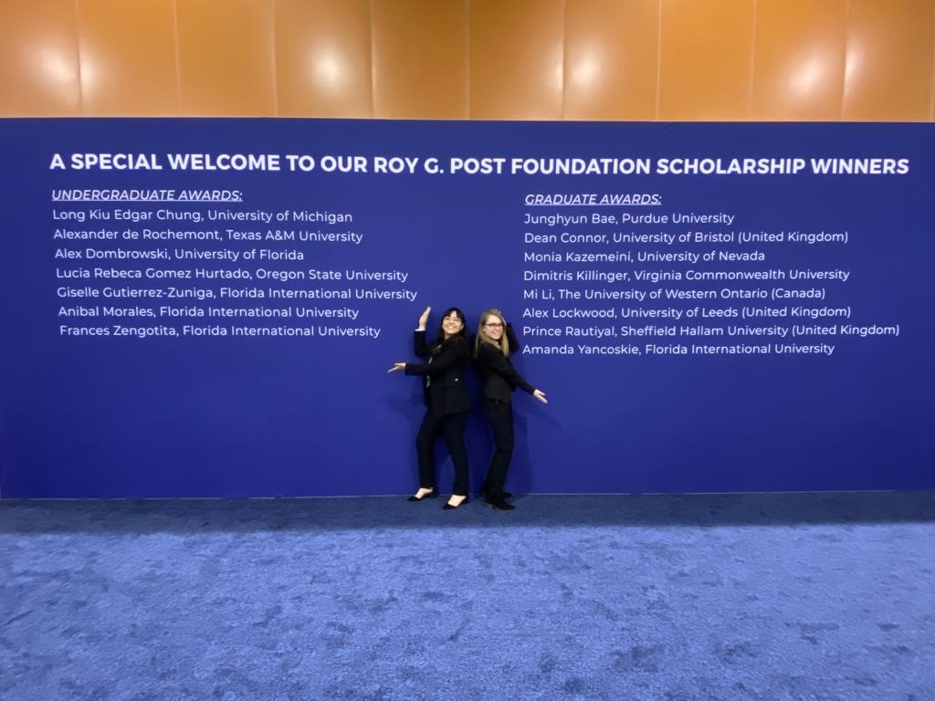 DOE Fellows Amanda Yancoskie and Gisselle Gutierrez-Zuniga standing in front of the Roy G. Post foundation winners' banner.